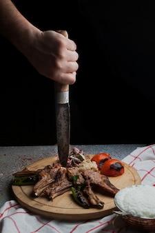 Widok z boku żeberka kebab ze smażonymi warzywami i posiekaną cebulą, ludzką ręką i nożem oraz ayran w drewnianej tacy na żywność