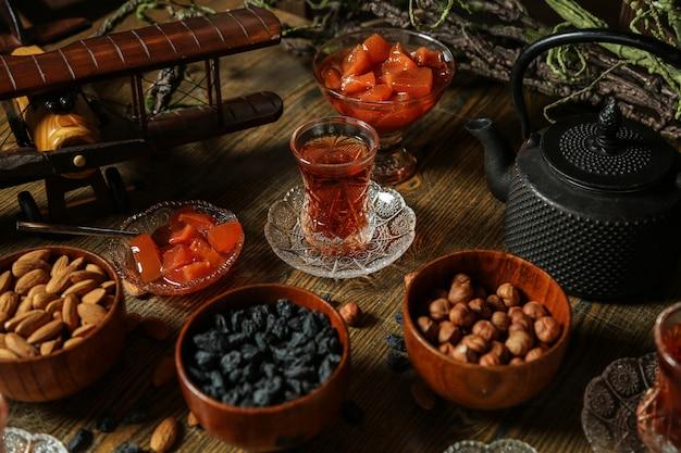 Widok z boku zestaw do herbaty rodzynki migdały orzechy dżem pigwowy z herbatą na stole