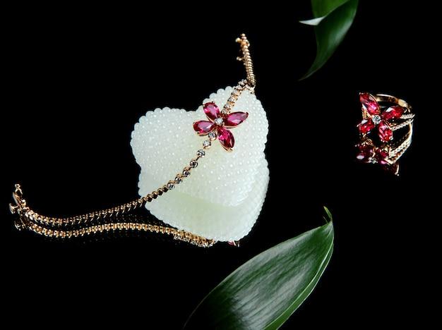 Widok z boku zestawu biżuterii ze złotej bransoletki i skórki z brylantami i rubinami w kształcie motyla