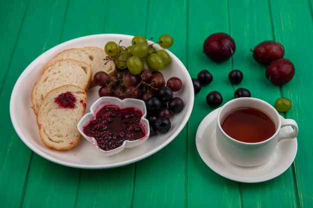 Widok z boku zestawu śniadaniowego z kromkami chleba dżemem malinowym i winogronem na talerzu i filiżanką herbaty z polewkami na zielonym tle