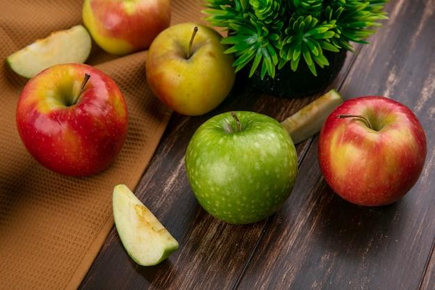 Widok z boku zielone i czerwone jabłka na brązowym ręczniku na drewnianym tle