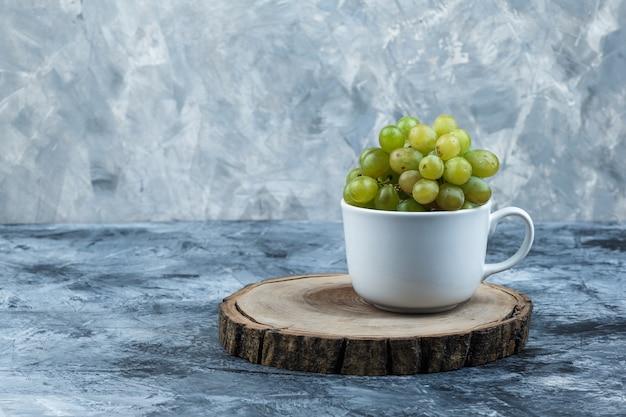 Widok z boku zielone winogrona w białym kubku na tle nieczysty tynku i kawałka drewna. poziomy