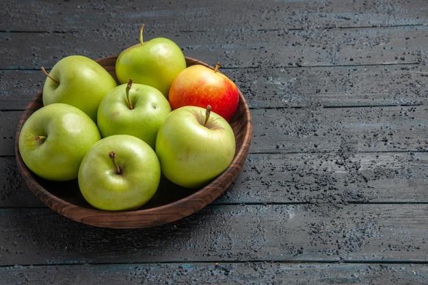 Widok z boku zielono-żółto-czerwonawe jabłka brązowa miska zielonych żółtych czerwonawych jabłek po lewej stronie szarego stołu