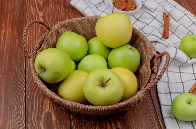Widok z boku zielonych i żółtych jabłek w koszu z dżemem jabłkowym i cynamonem na kraciastym materiale i drewnianym stole
