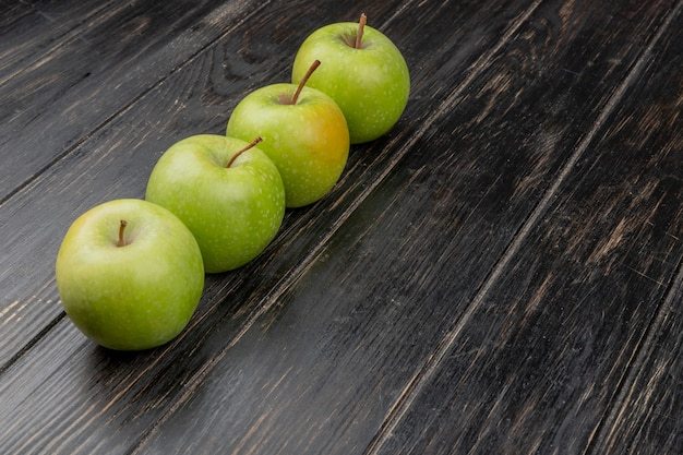 Widok z boku zielonych jabłek na powierzchni drewnianych