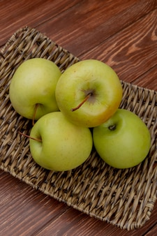 Widok z boku zielonych jabłek w koszu na talerz na powierzchni drewnianych