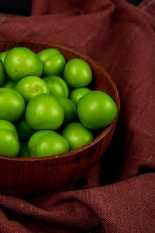 Widok z boku zielonych kwaśnych śliwek w drewnianej misce na ciemno czerwonym stole z tkaniny