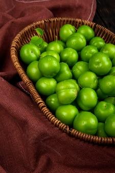 Widok z boku zielonych kwaśnych śliwek w wiklinowym koszu na ciemnoczerwonym stole z tkaniny
