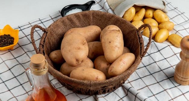 Widok z boku ziemniaków w koszu z masłem, solą, czarnym pieprzem na kraciastym płótnie i białym stole