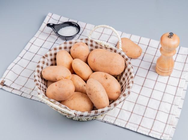 Widok z boku ziemniaków w koszu z solą na kraciastym płótnie na niebieskiej powierzchni
