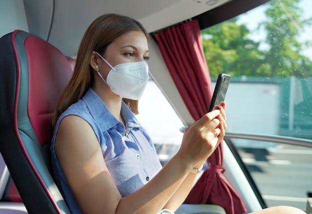 Widok z boku zrelaksowanej kobiety z maską kn95 ffp2 za pomocą aplikacji na smartfona. pasażer autobusu w masce ochronnej podróżujący wysyłając sms-y na telefon komórkowy.