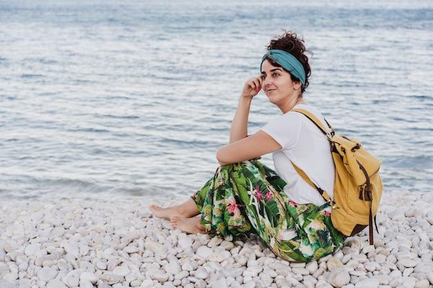 Widok z boku zrelaksowany kaukaski kobieta z żółtym plecakiem siedząc na plaży podczas zachodu słońca. czas letni. marzyć. styl życia na zewnątrz