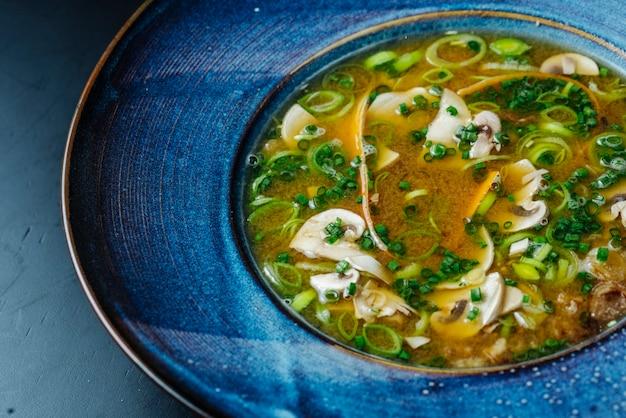 Widok z boku zupa grzybowa i zielona cebula w talerzu