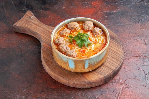 Widok z boku zupy pomidorowej z klopsikami z makaronem w brązowej misce na ciemnym tle