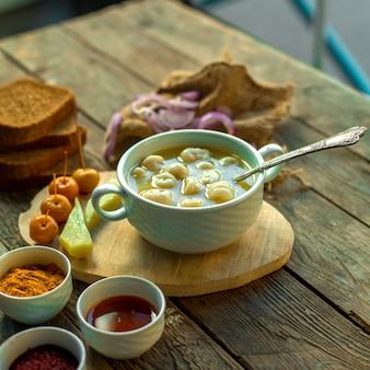 Widok z boku zupy z pierogów dushbara w białej misce z piklami