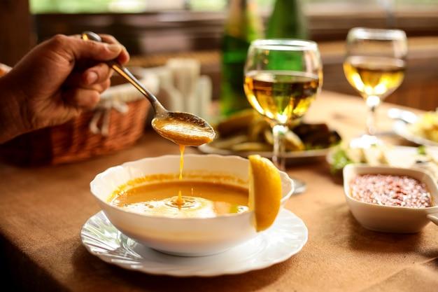 Widok z boku zupy z soczewicy merci w misce i dłoni z łyżką nad misą