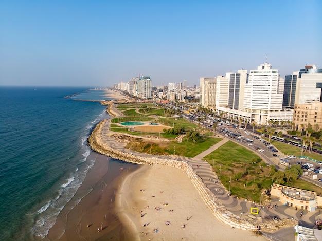 Widok z brzegu na nowoczesną dzielnicę tel awiwu. widok z góry na stolicę izraela. czysta piękna plaża w centrum metropolii na tle wysokich drapaczy chmur.
