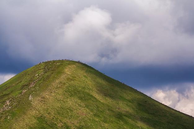 Widok z daleka oświetlonej letnim słońcem górskim hoverla z mnóstwem ludzi podróżujących w górę i na dół trasą turystyczną pod jasnym błękitnym niebem. piękno przyrody, niebezpieczeństwo dla ekologii, turystyka i turystyka.