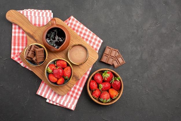 Widok z daleka z góry truskawki i czekoladowe truskawki czekolada i krem czekoladowy w misce na brązowej desce do krojenia obok talerza z truskawkami i czekoladą