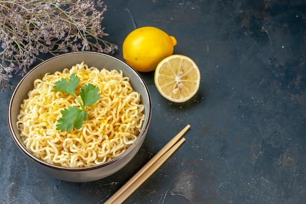 Widok z dołu azjatycki makaron ramen w misce z cytryną i pokrojonymi pałeczkami z cytryny suszona gałąź kwiatowa na ciemnym stole wolna przestrzeń