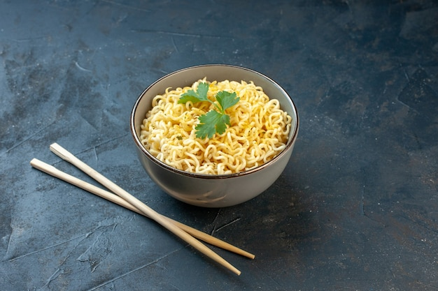 Widok z dołu azjatycki makaron ramen z kolendrą w misce pałeczkami na ciemnym stole