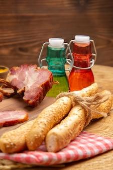 Widok z dołu becon kroi czerwone i zielone butelki chleba na brązowej powierzchni