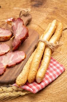 Widok z dołu becon plastry na drewnianej desce chleb na drewnianym stole