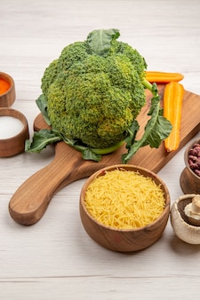 Widok z dołu brokuły pokrojone marchewki na desce do krojenia sól czerwona papryka miska z cienkimi rurkami makaronu grzyb na szarym stole
