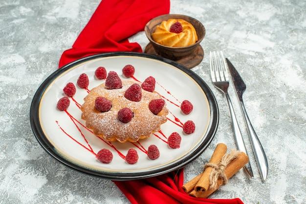 Widok z dołu ciasto jagodowe na białym owalnym talerzu czerwony szal herbatnik widelec i nóż do obiadu laski cynamonu na szarej powierzchni