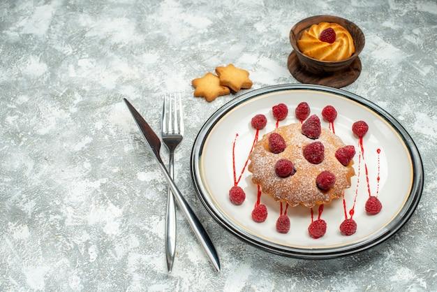 Widok z dołu ciasto jagodowe na białym owalnym talerzu herbatniki skrzyżowane widelec i nóż obiadowy na szarej powierzchni wolnej przestrzeni