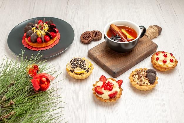 Widok z dołu ciasto jagodowe na szarym talerzu tarty filiżankę cytrynowo-cynamonowej herbaty na desce do krojenia ciasteczka i liście sosny z świąteczną zabawką na białym drewnianym tle