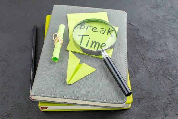 Widok z dołu czas przerwy napisany na karteczkach samoprzylepnych czarny ołówek lupa na notatnikach na ciemnym stole