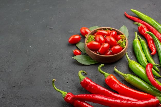 Widok z dołu czerwona i zielona papryka i miskę pomidorów cherry po prawej stronie czarnym tłem