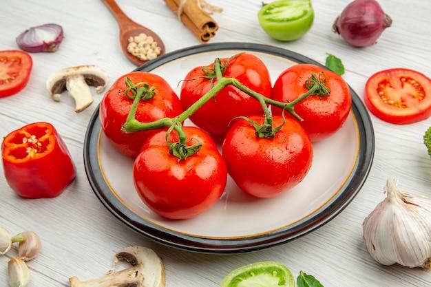 Widok z dołu czerwone pomidory na białym talerzu czosnek grzyby anyż czarnooki groszek w drewnianej łyżce laski cynamonu cebula na szarym stole