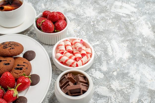 Widok z dołu do połowy ciasteczka truskawki i okrągłe czekoladki na owalnym talerzu miski cukierków truskawki czekoladki i herbata cynamonowa po lewej stronie szaro-białego stołu
