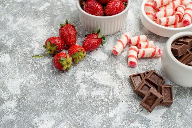 Widok z dołu do połowy misek z truskawkami, czekoladkami, cukierkami i kilkoma truskawkowymi czekoladkami, cukierkami po prawej stronie szaro-białego stołu