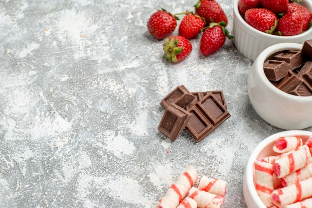 Widok z dołu do połowy miski z truskawkami, czekoladkami, cukierkami i niektórymi truskawkami, czekoladkami, cukierkami po prawej stronie szaro-białego tła mozaiki