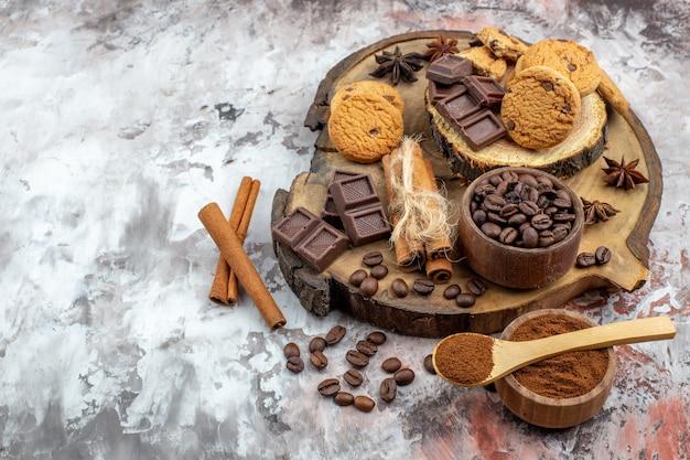 Widok z dołu drewniana deska z miską z palonymi ziarnami kawy czekolada laski cynamonu herbatniki kakao miska na stole z wolnym miejscem