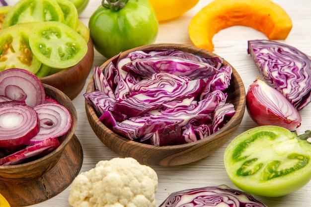 Widok z dołu drewniane miski z cebulą, czerwoną kapustą, zielonym pomidorem, kalafiorem, pokrojoną dynią na białym drewnianym stole