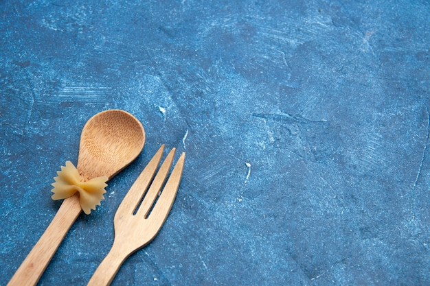 Widok z dołu drewniany widelec łyżka farfalle na łyżce na niebieskim stole wolna przestrzeń