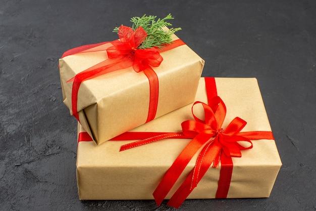 Widok z dołu duże i małe prezenty świąteczne w brązowym papierze przewiązane czerwoną wstążką na ciemnym