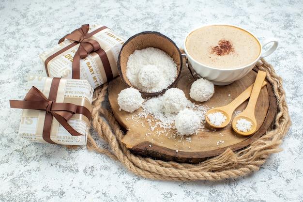 Widok z dołu filiżanka cappuccino miska proszku kokosowego drewniane łyżki na drewnianej desce prezenty na szarym tle