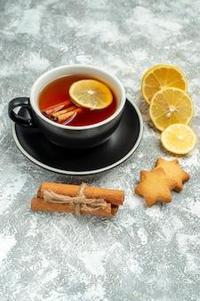 Widok z dołu filiżanka herbaty plasterki cytryny laski cynamonu na szarej powierzchni
