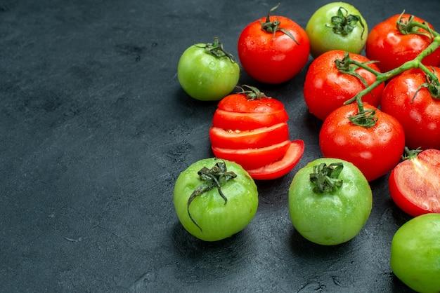 Widok z dołu gałąź pomidora posiekane pomidory zielone pomidory na czarnym stole z miejscem do kopiowania