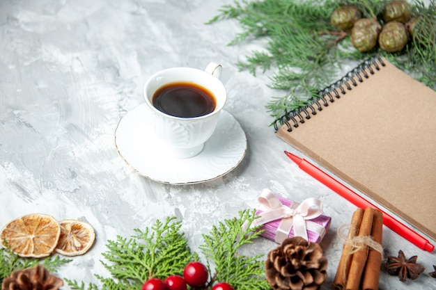 Widok z dołu gałęzie sosny filiżanka herbaty małe prezenty choinka zabawki notatnik ołówek na szarym tle