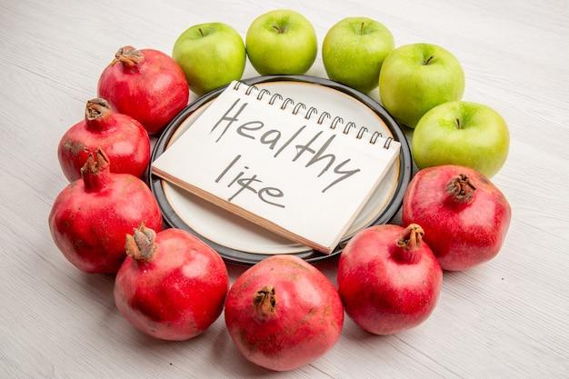 Widok z dołu granaty zielone jabłka zdrowe życie napisane w notatniku na talerzu na białym stole