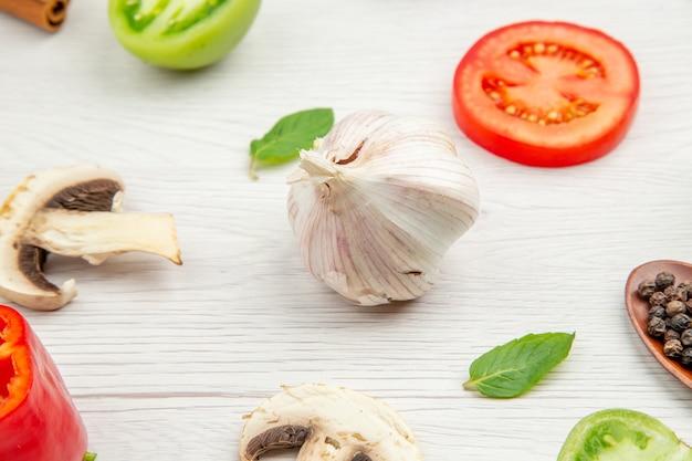 Widok z dołu grzyby czosnkowe zielone i czerwone pomidory liście mięty na szarym stole