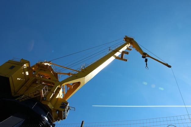 Widok z dołu kabiny i wysięgnika żółtego dźwigu portowego na tle nieba z białym samolotem foo