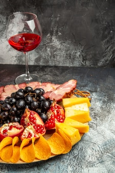 Widok z dołu kawałki sera mięso winogrona i granat na owalnej desce do serwowania kieliszek wina na ciemnym tle