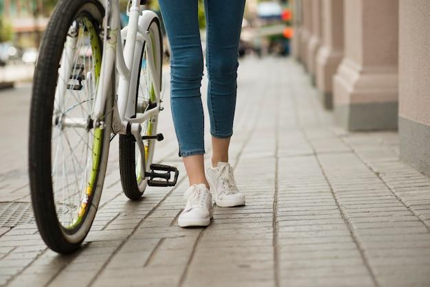 Widok z dołu kobiety idącej obok roweru